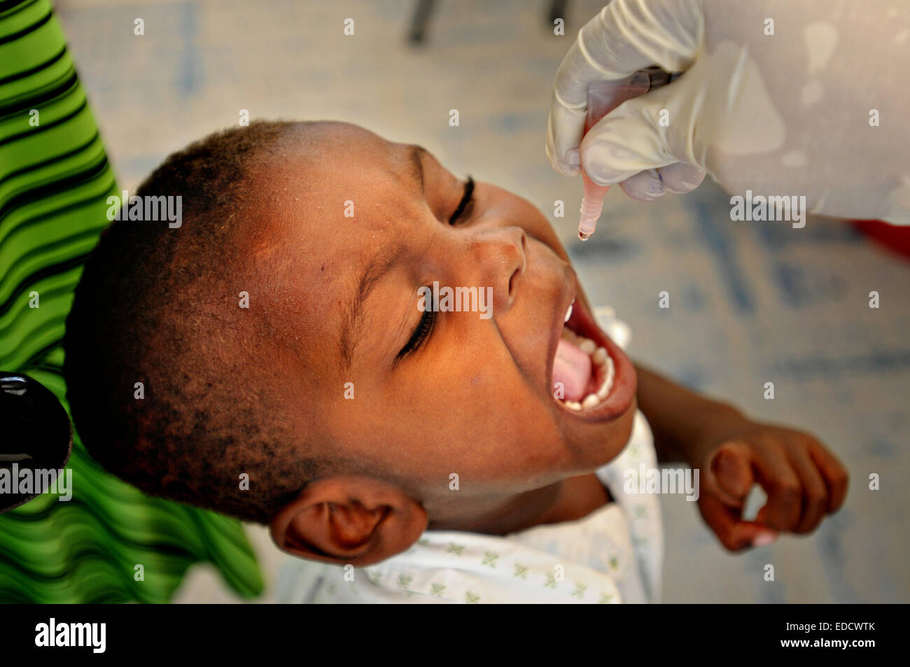 A young boy receives an oral polio vaccination at a medical clinic at Petionville golf club July 13, 2010 in Port - Stock Image