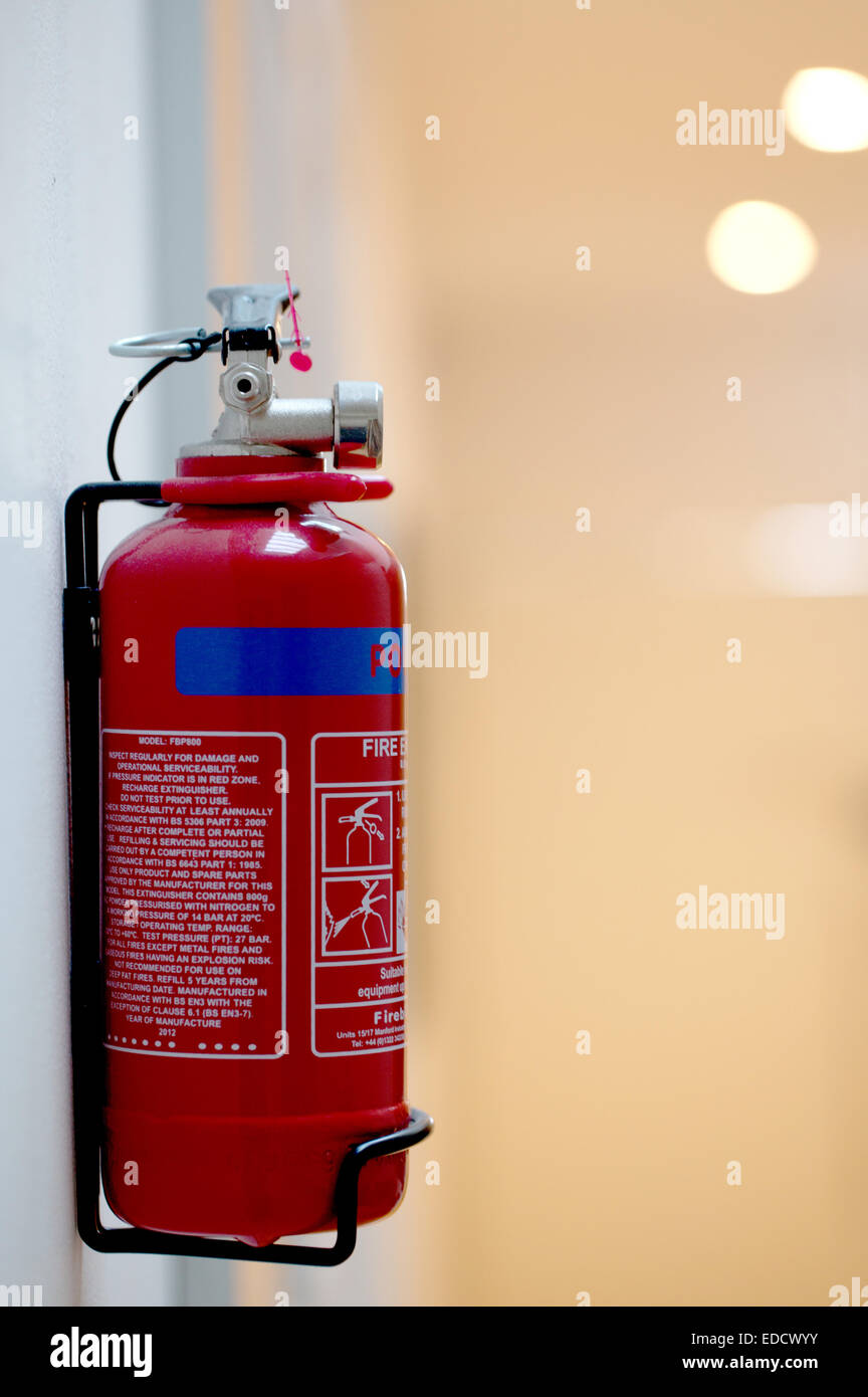 fire extinguisher hanging on wall - Stock Image