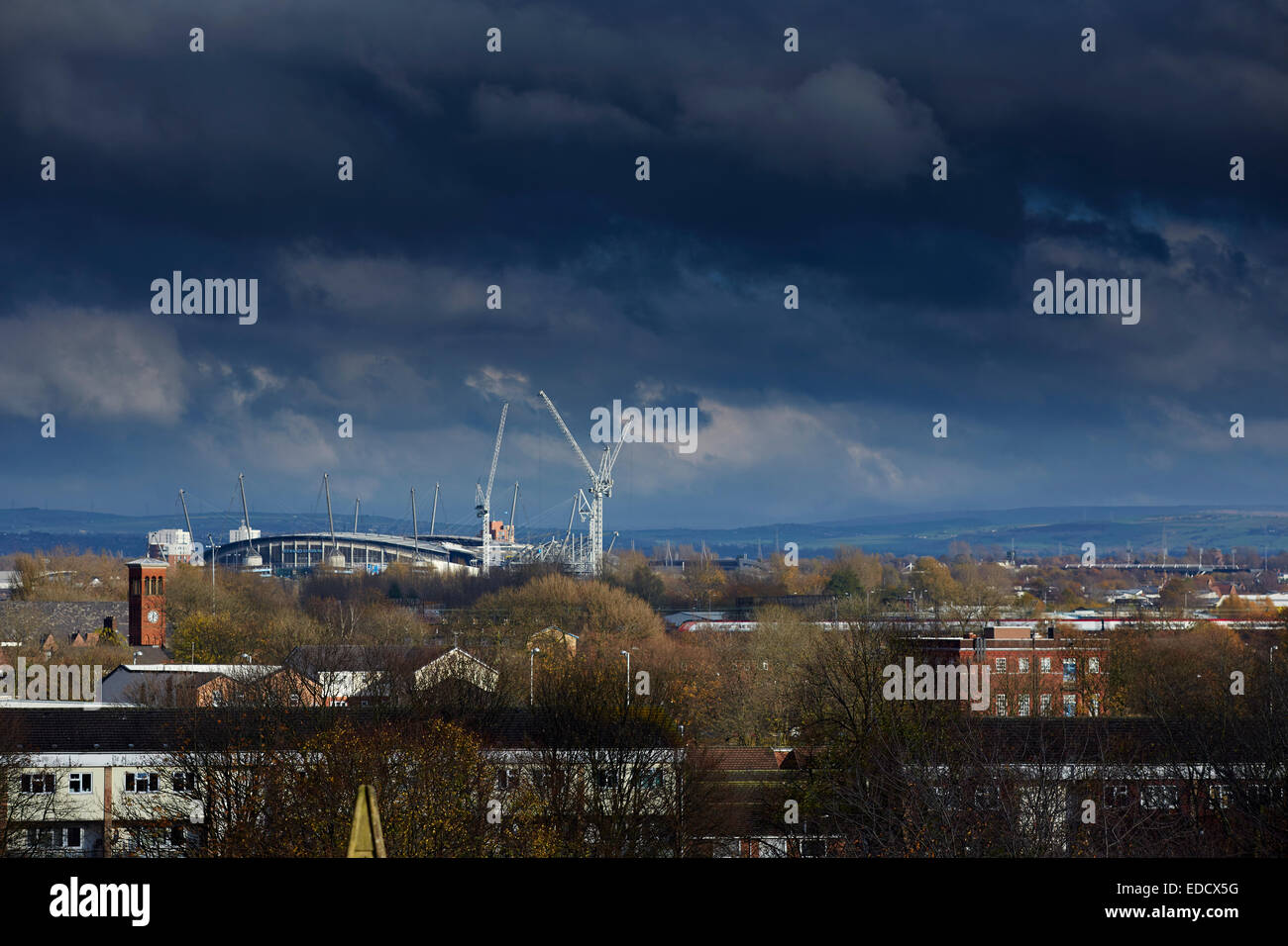 Manchester Etihad Stadium on the skyline with a Virgin train passing - Stock Image