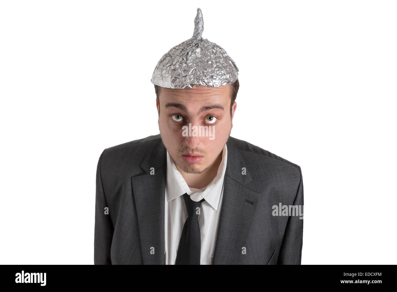 distraught looking conspiracy believer in suit with aluminum foil head isolated on white background - Stock Image