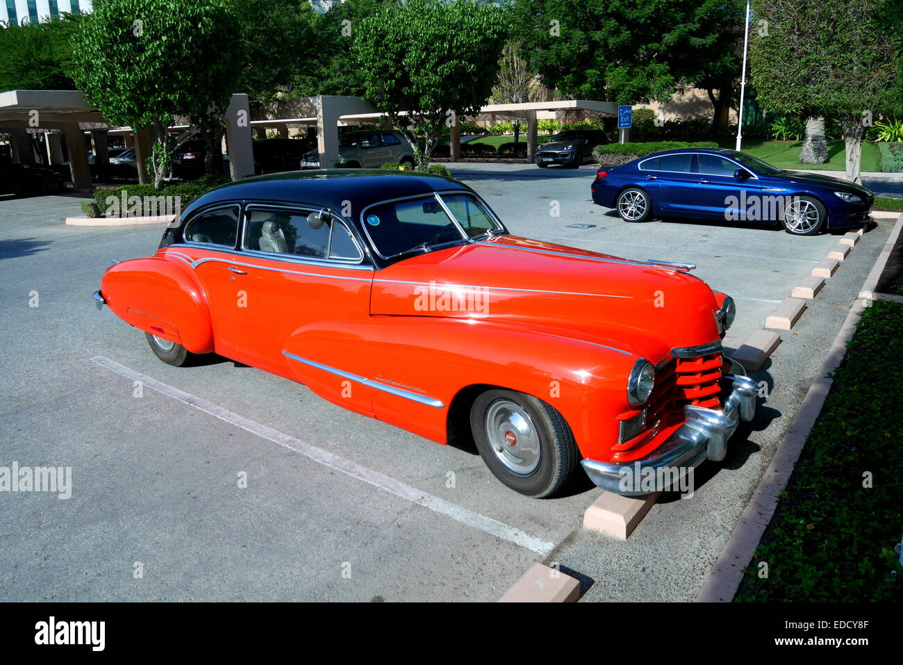 Cadillac 62 series with BMW behind in the car park of the Ritz Carlton Hotel, Kingdom of Bahrain - Stock Image