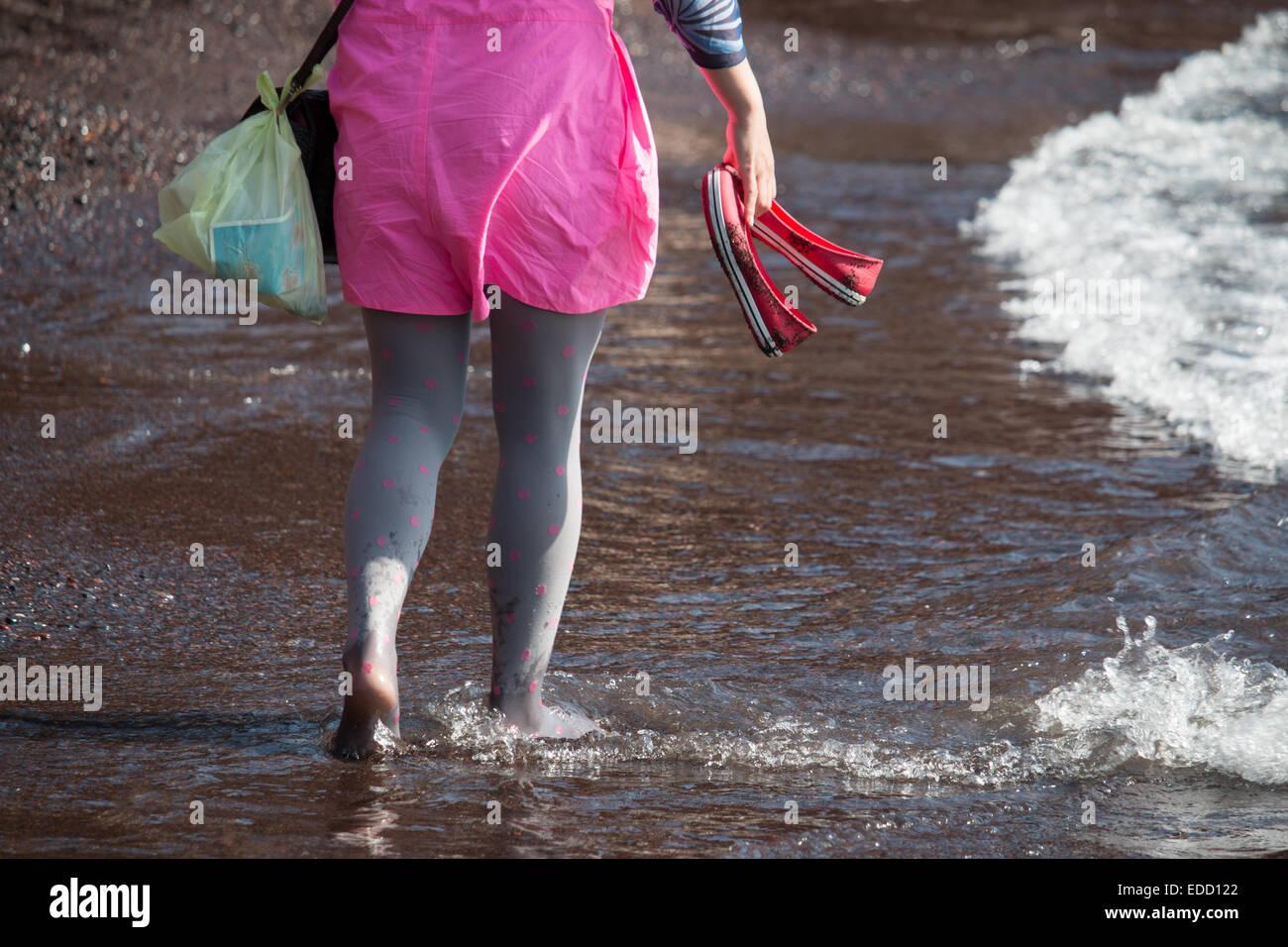 Girl in pantyhose and pink dress walking down a beach, Santorini, Cyclades, Greek islands, Greece Stock Photo