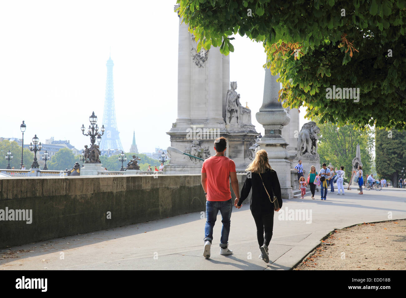 Couple walking towards the Pont Alexandre III bridge in Paris, in Autumn, the Eiffel Tower behind, France, Europe - Stock Image