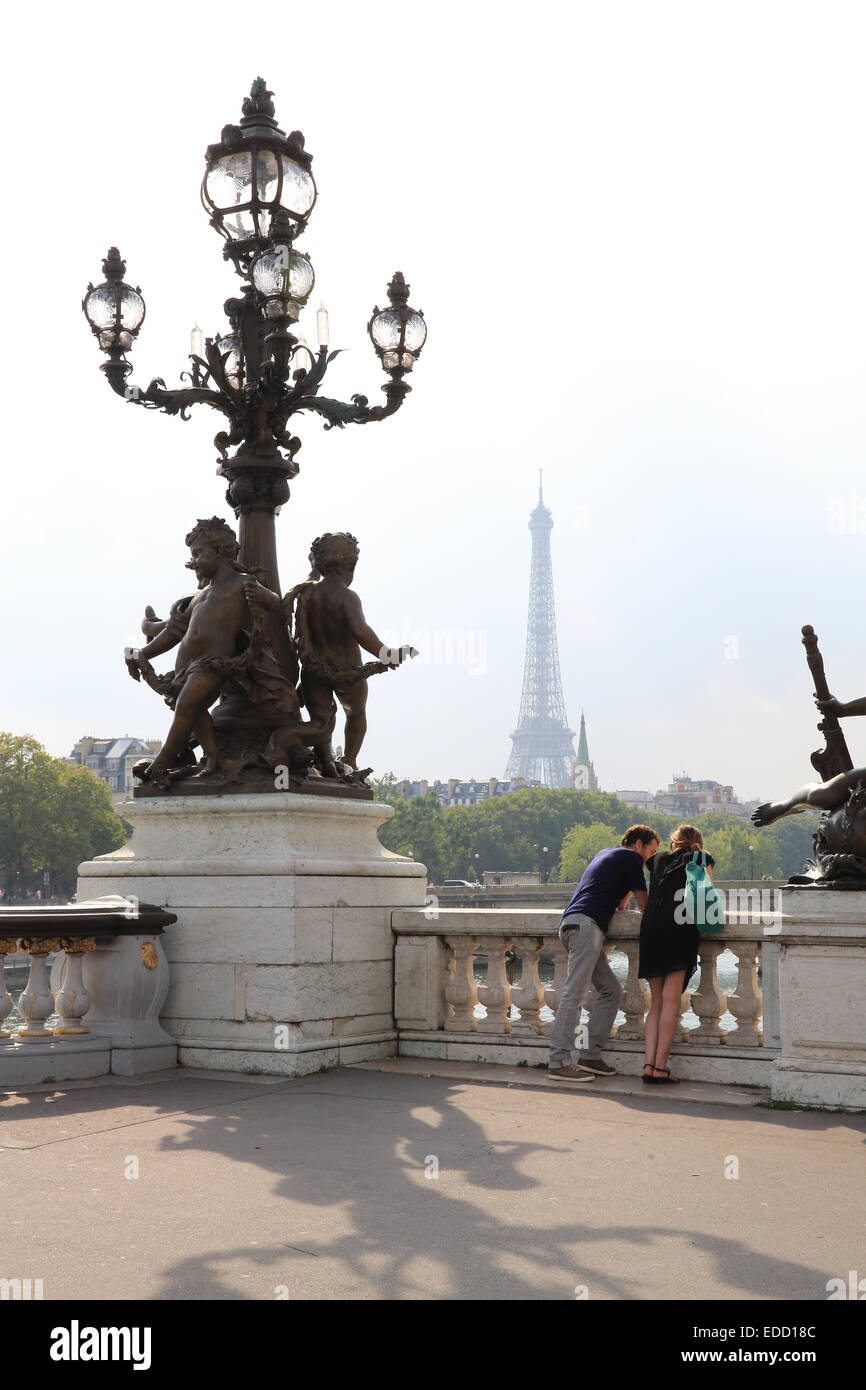 A young couple on the Pont Alexandre III bridge in Paris in Autumn, with the Eiffel Tower behind, in France, Europe - Stock Image