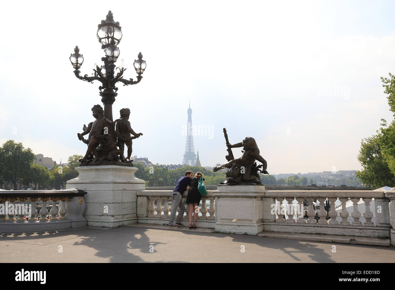 A young couple on the Pont Alexandre III bridge in Paris in Autumn, with the Eiffel Tower behind, in France, Europe Stock Photo
