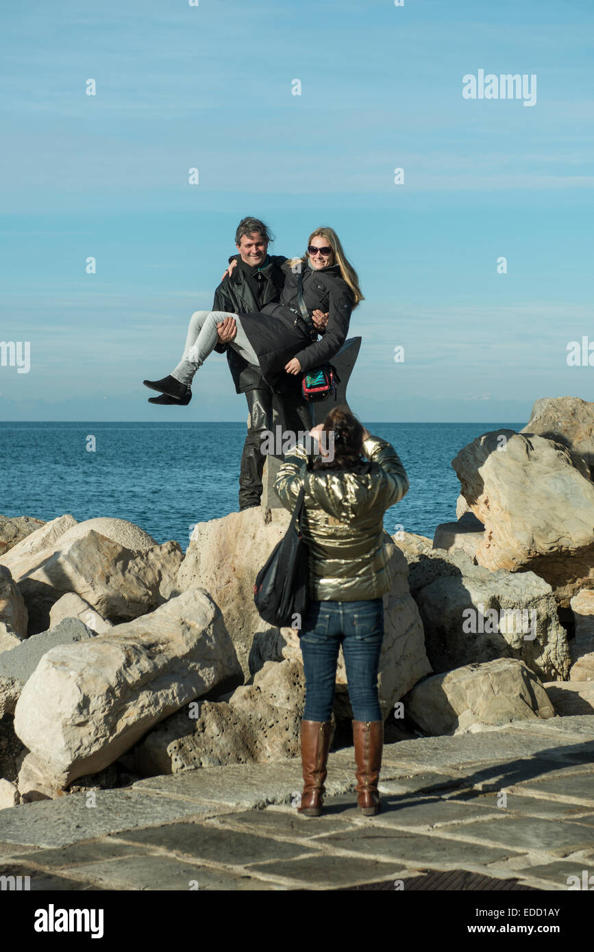 a photograph of a group of people in front of the sea - Stock Image
