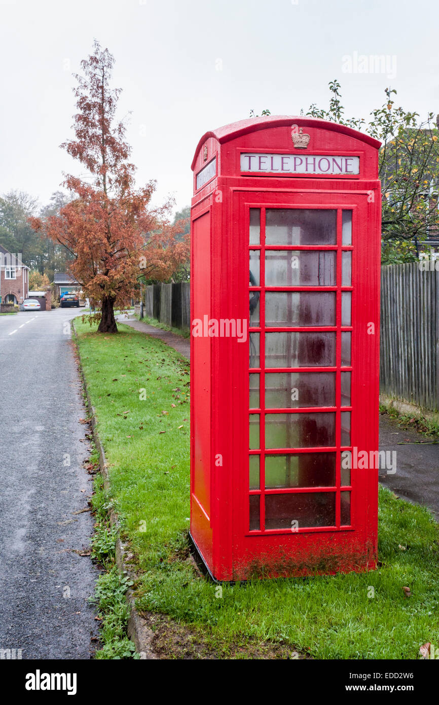 Traditional British red telephone kiosk on a suburban street. - Stock Image