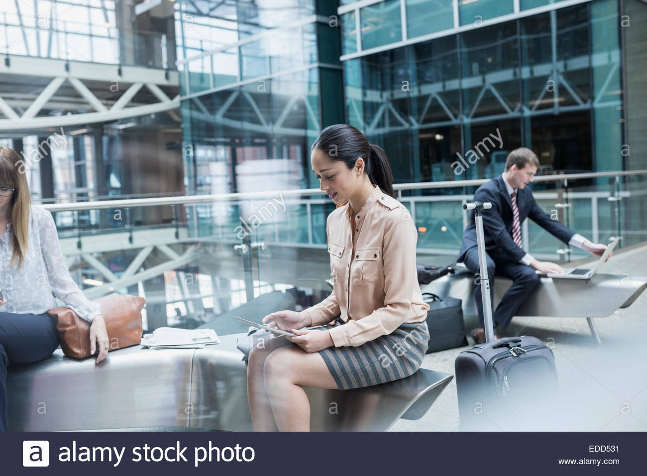 Business people using technology in airport atrium - Stock Image