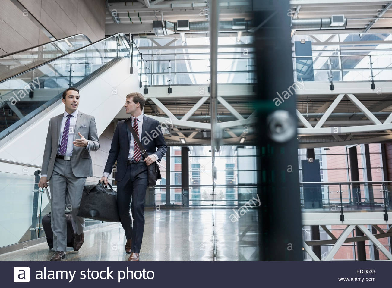 Businessmen talking and walking with luggage in airport - Stock Image