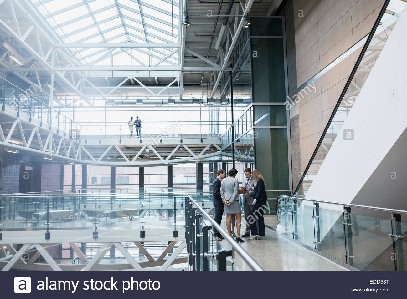 Business people meeting in atrium - Stock Image