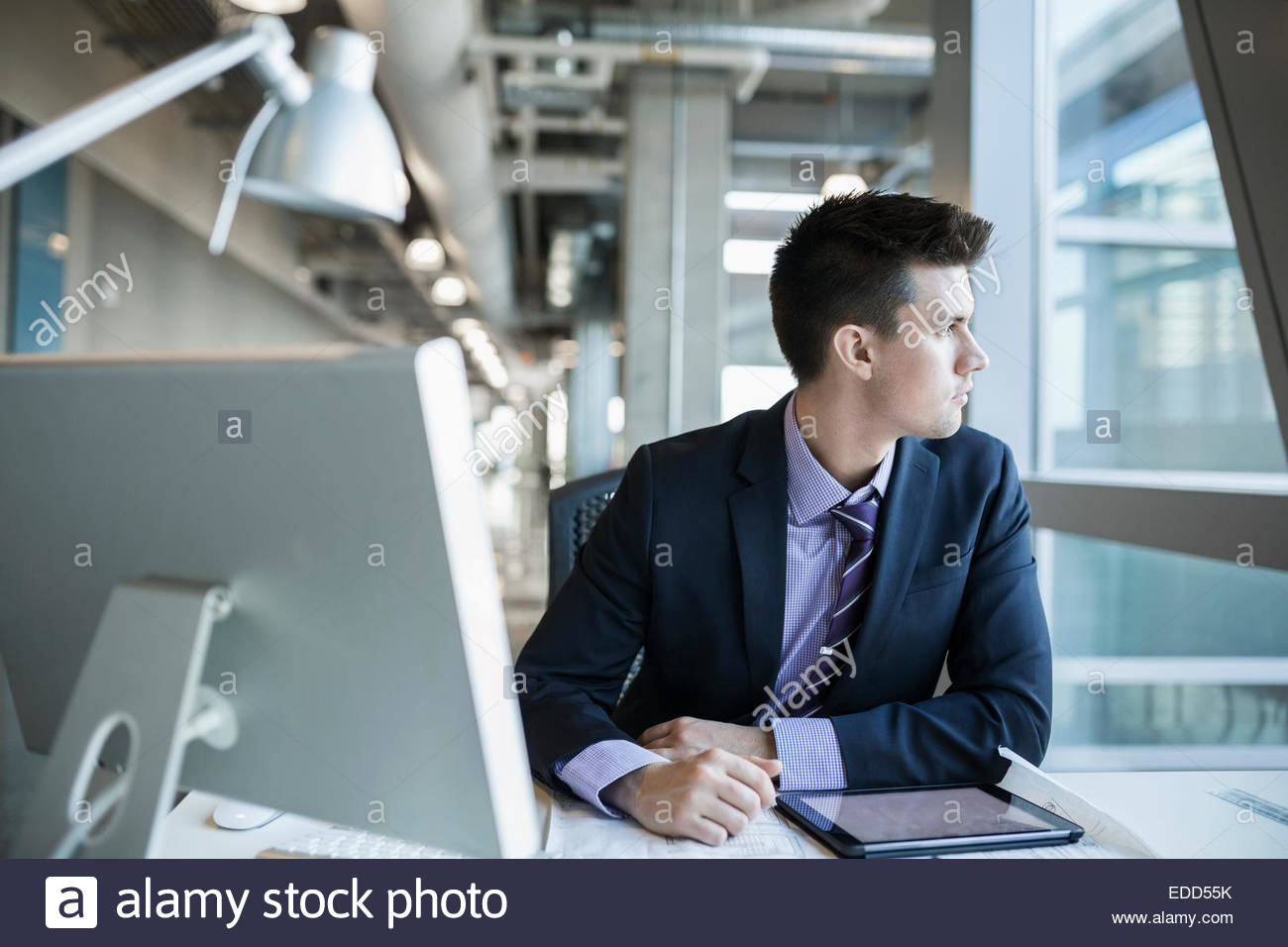 Pensive businessman looking out window - Stock Image