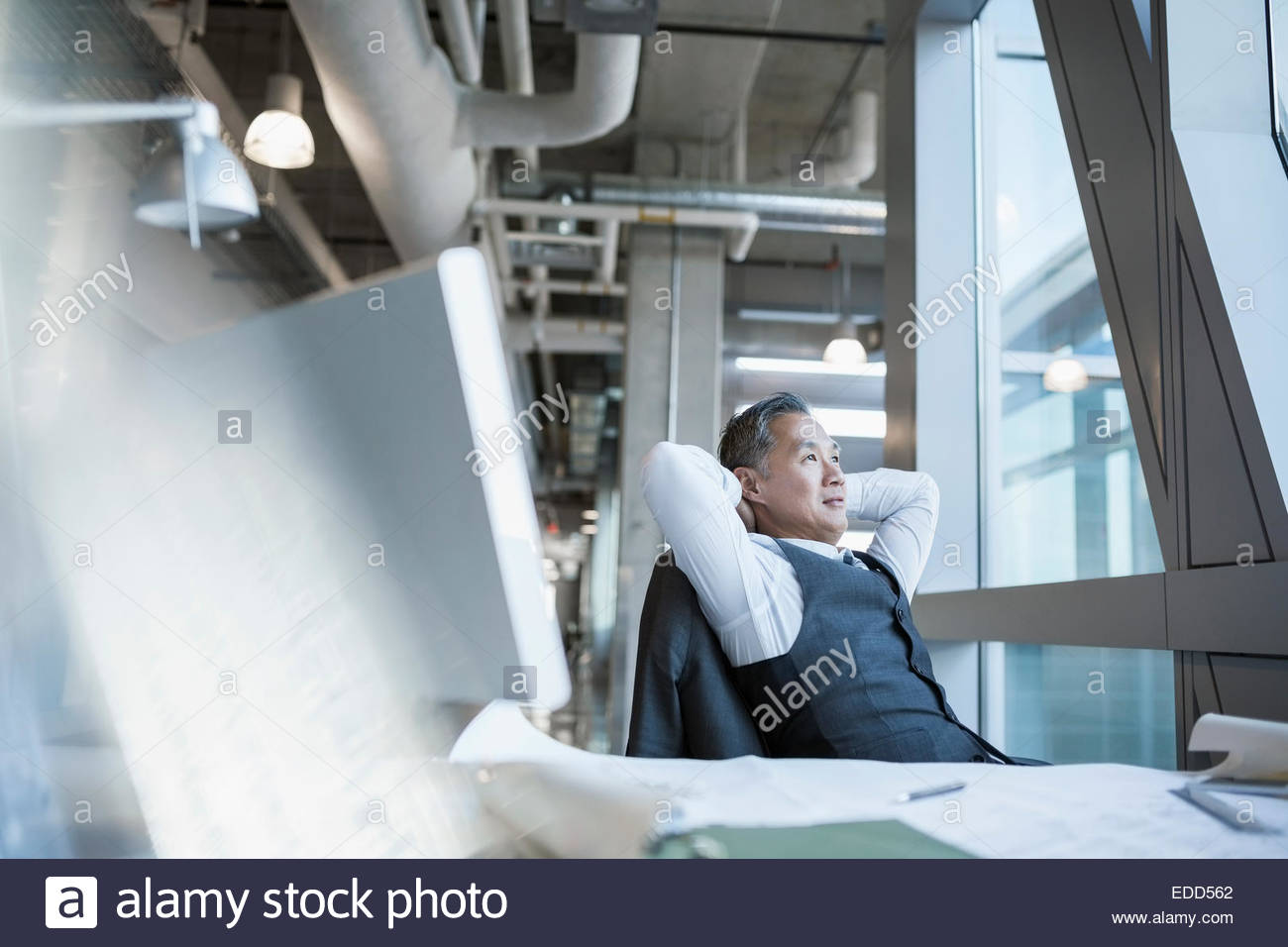 Pensive architect with hands behind head - Stock Image