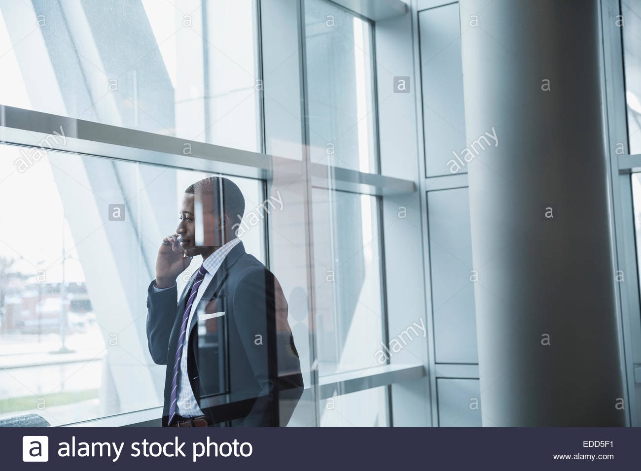 Businessman talking on cell phone at window Stock Photo