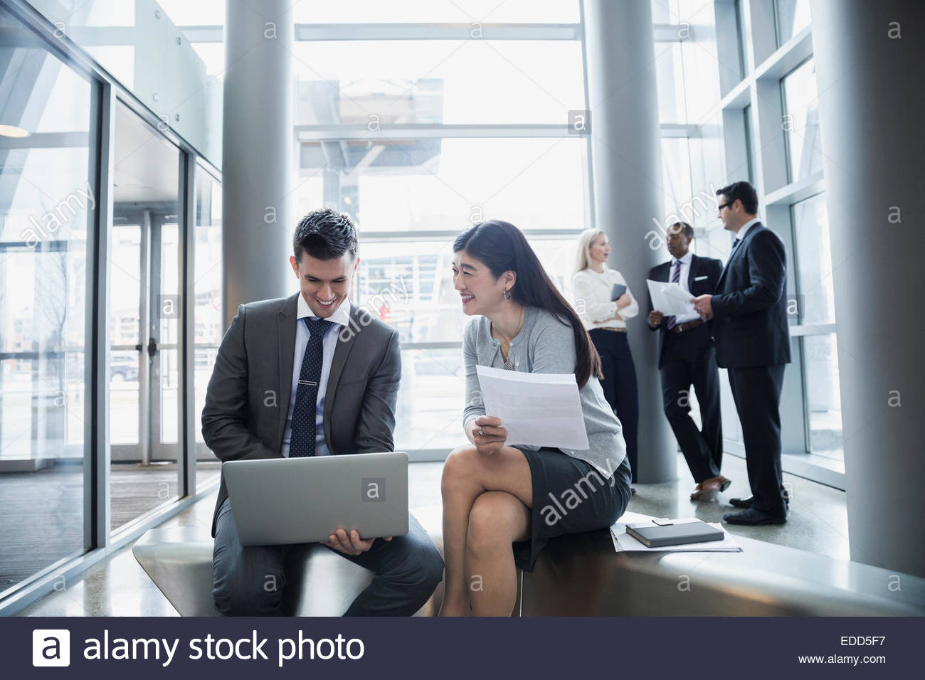Businessman and businesswoman using laptop - Stock Image