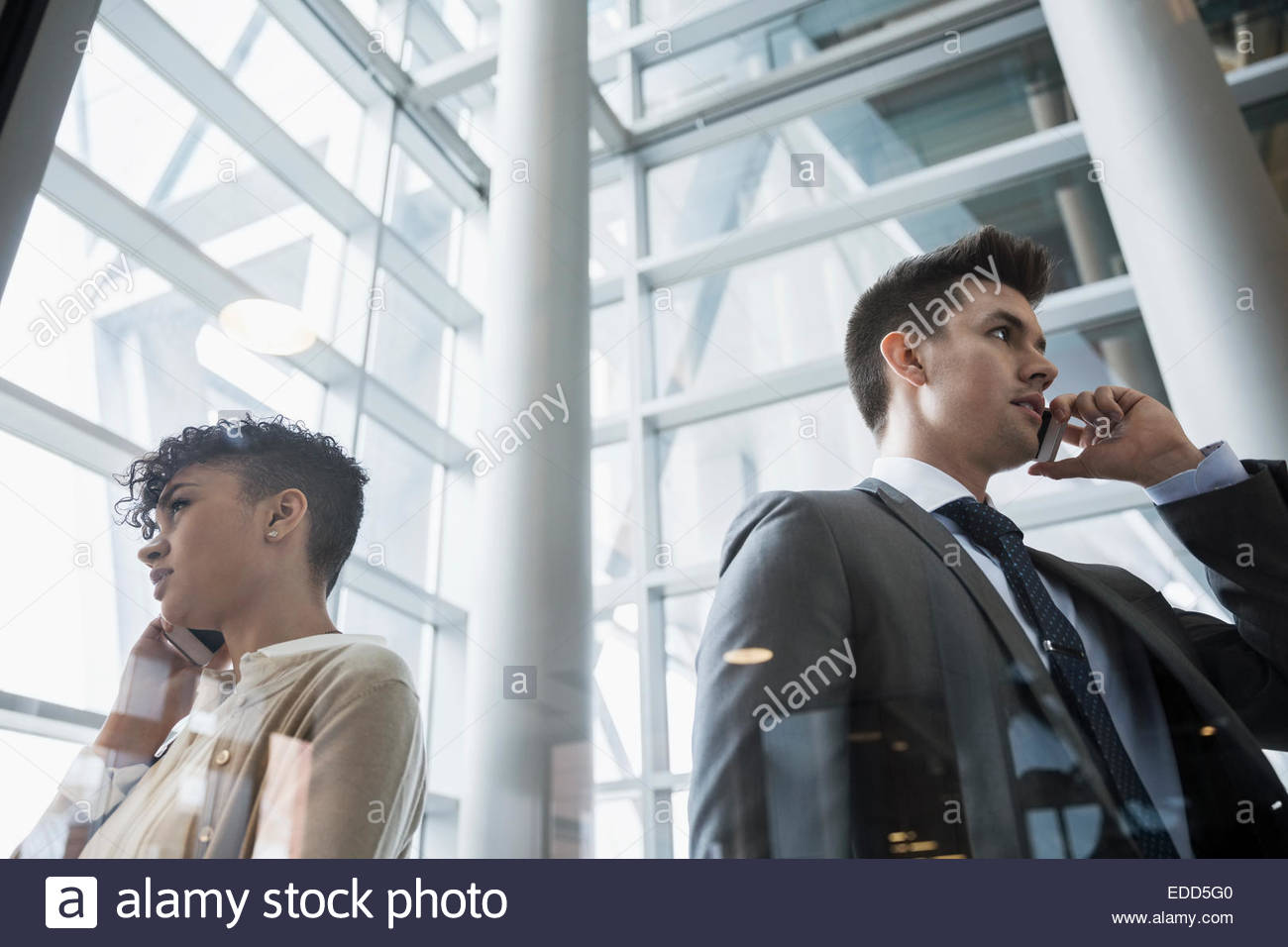 Businessman and businesswoman talking on cell phones - Stock Image