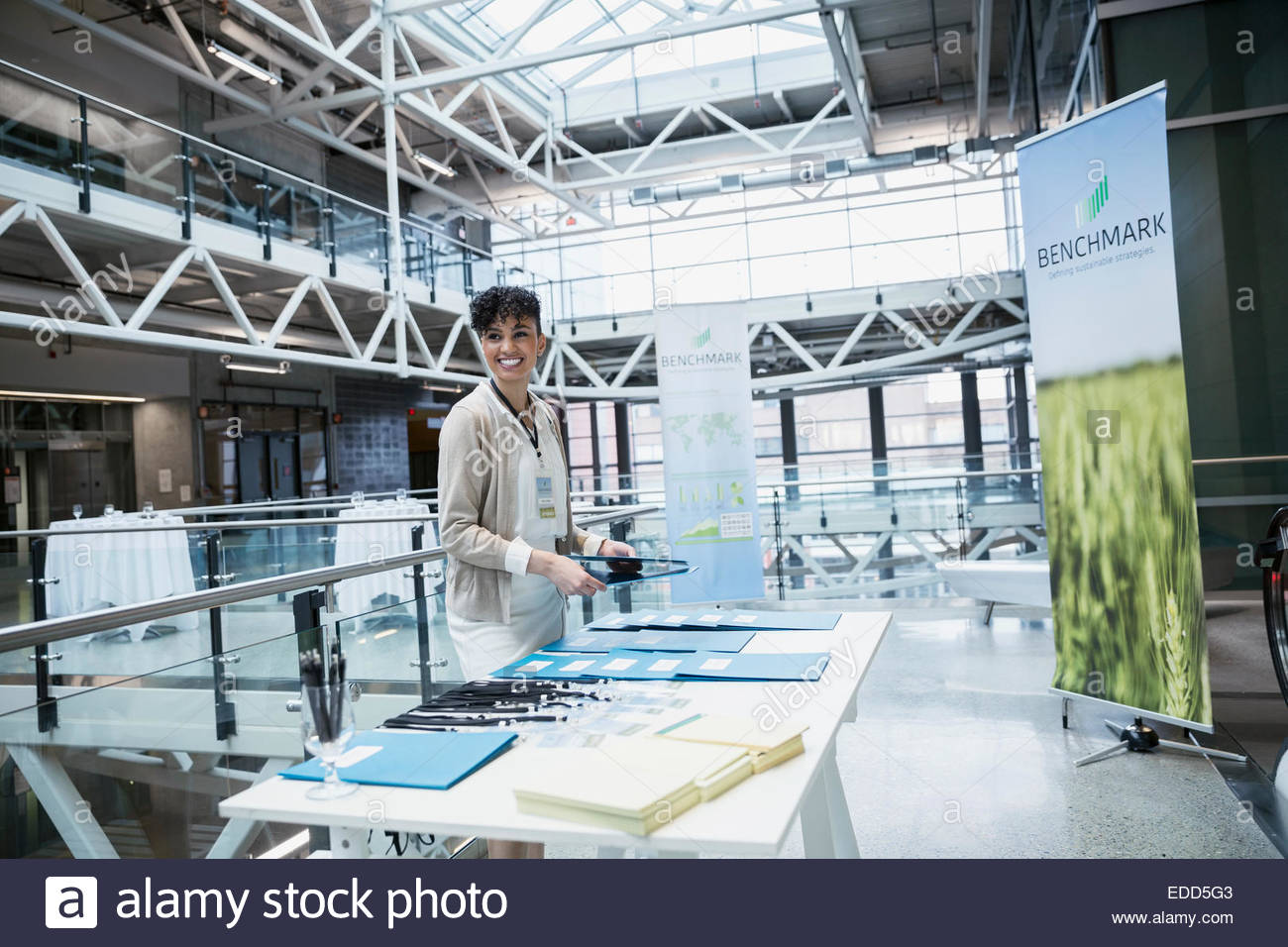 Smiling businesswoman at conference registration table - Stock Image