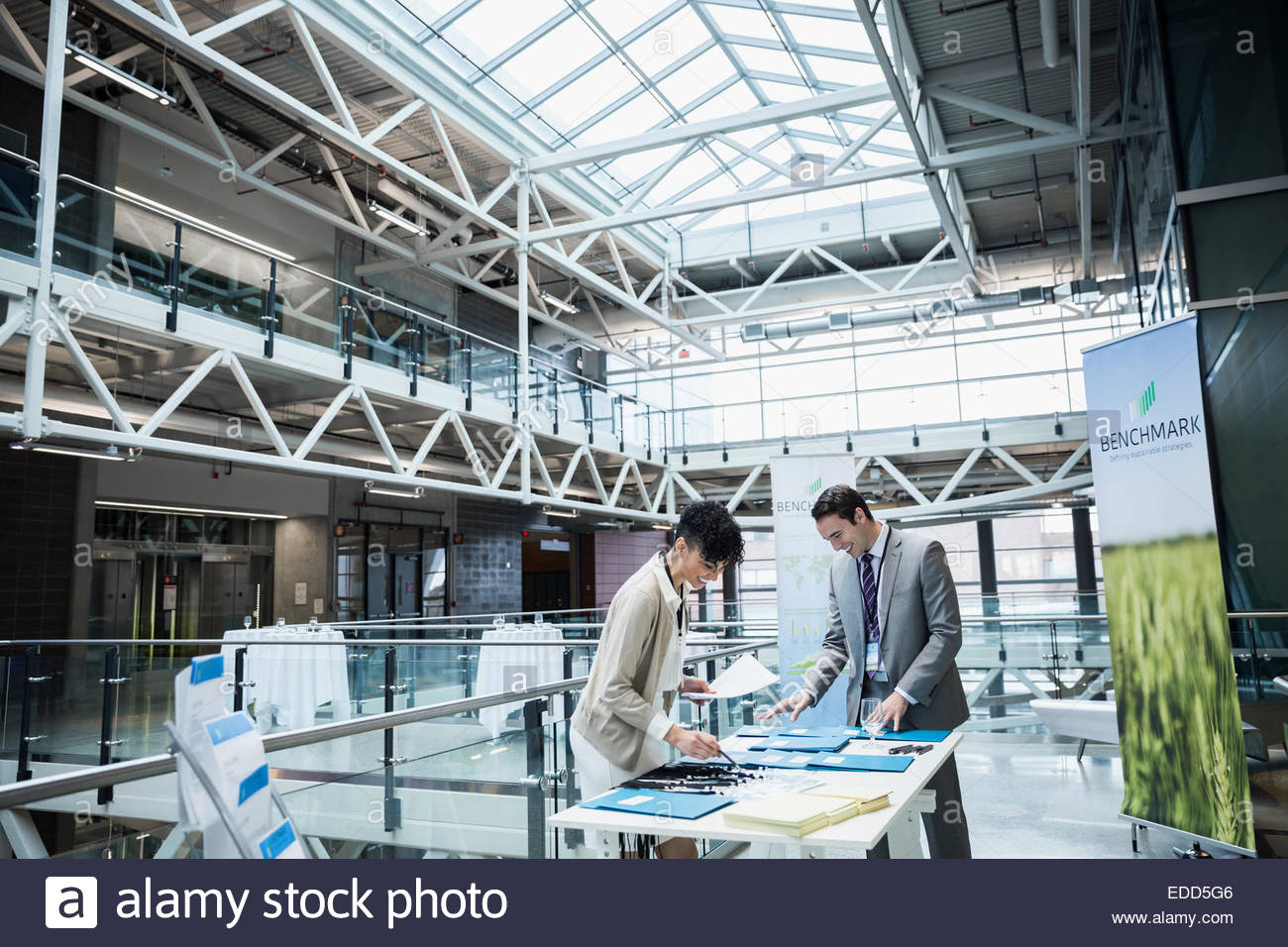 Businessman checking in at conference registration table - Stock Image