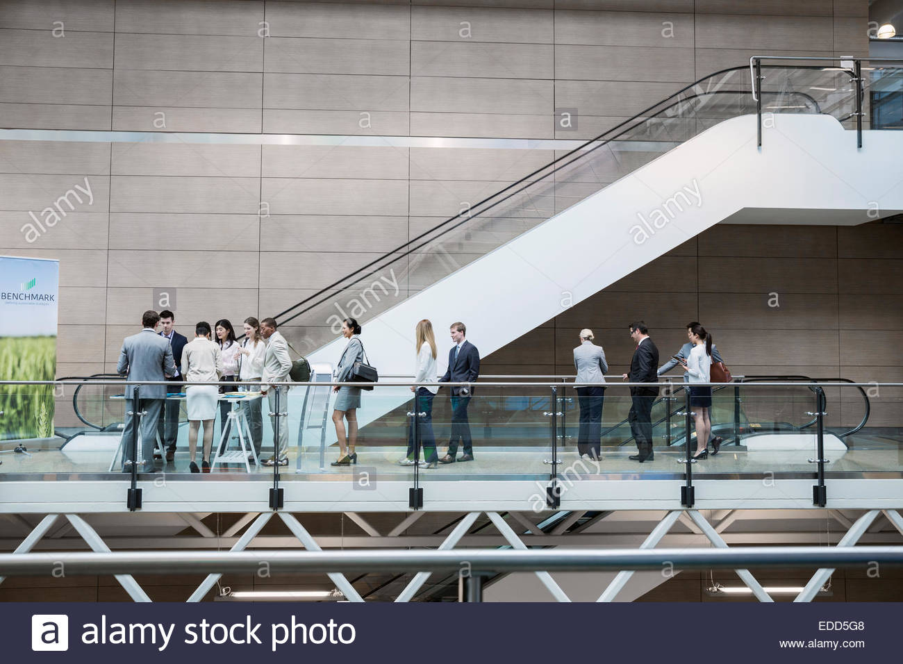 Business people checking in at conference registration table - Stock Image