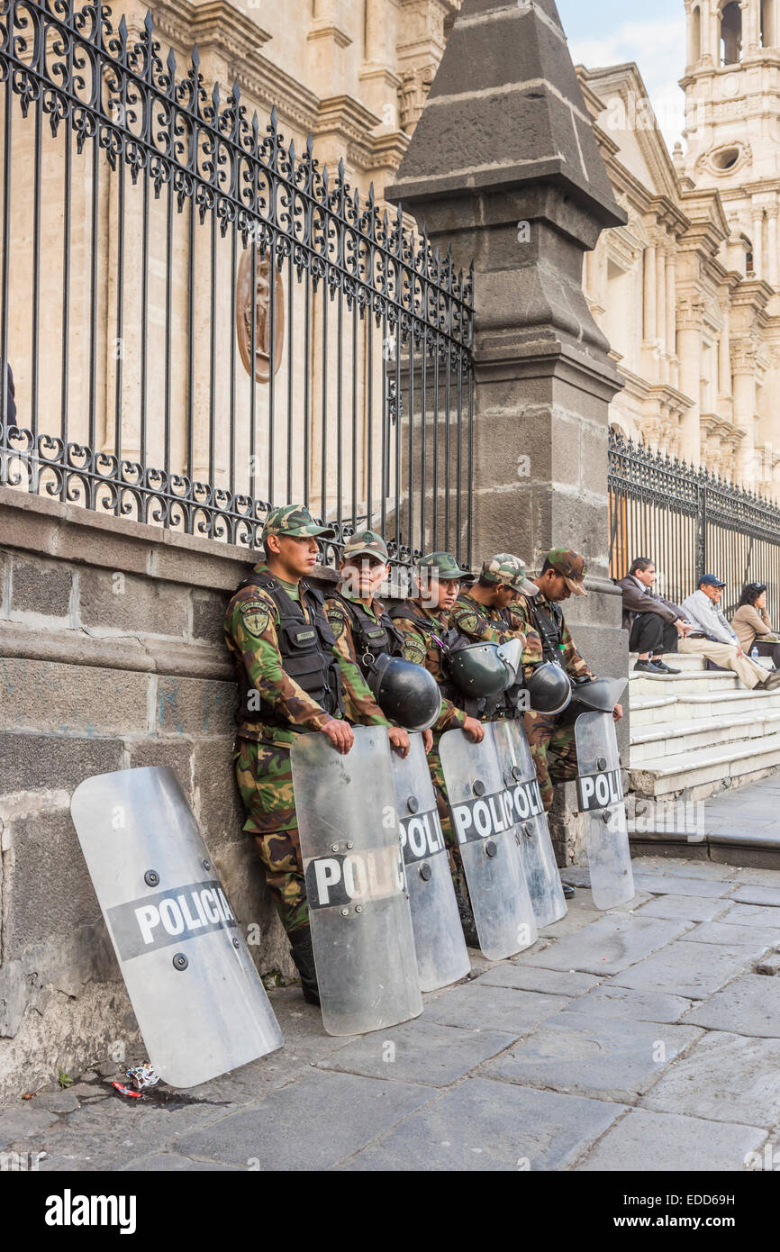Peruvian riot police wearing camouflage uniform with shields and helmets standing outside Arequipa Cathedral, Plaza - Stock Image
