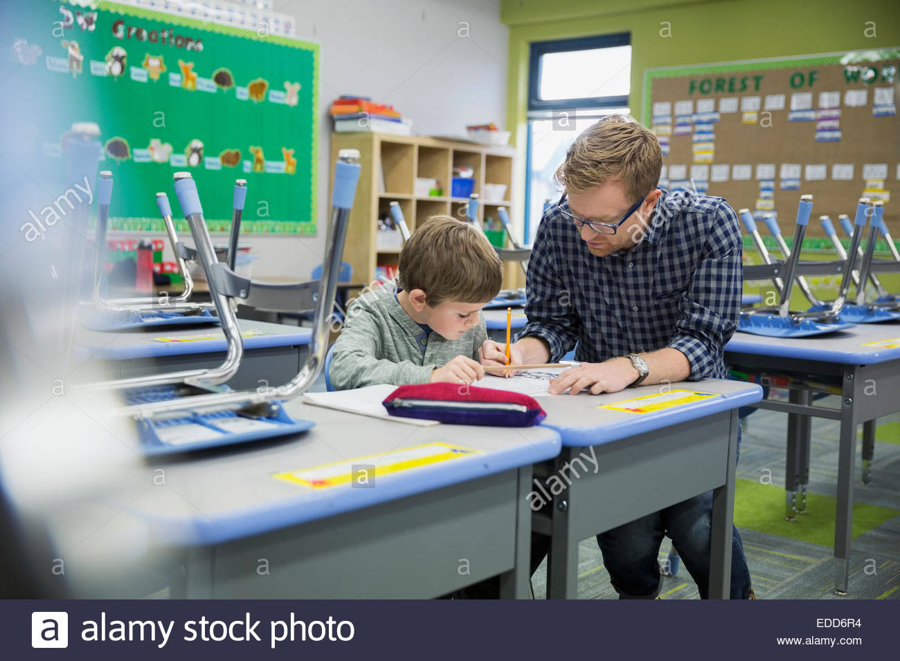 Teacher helping elementary student in classroom - Stock Image