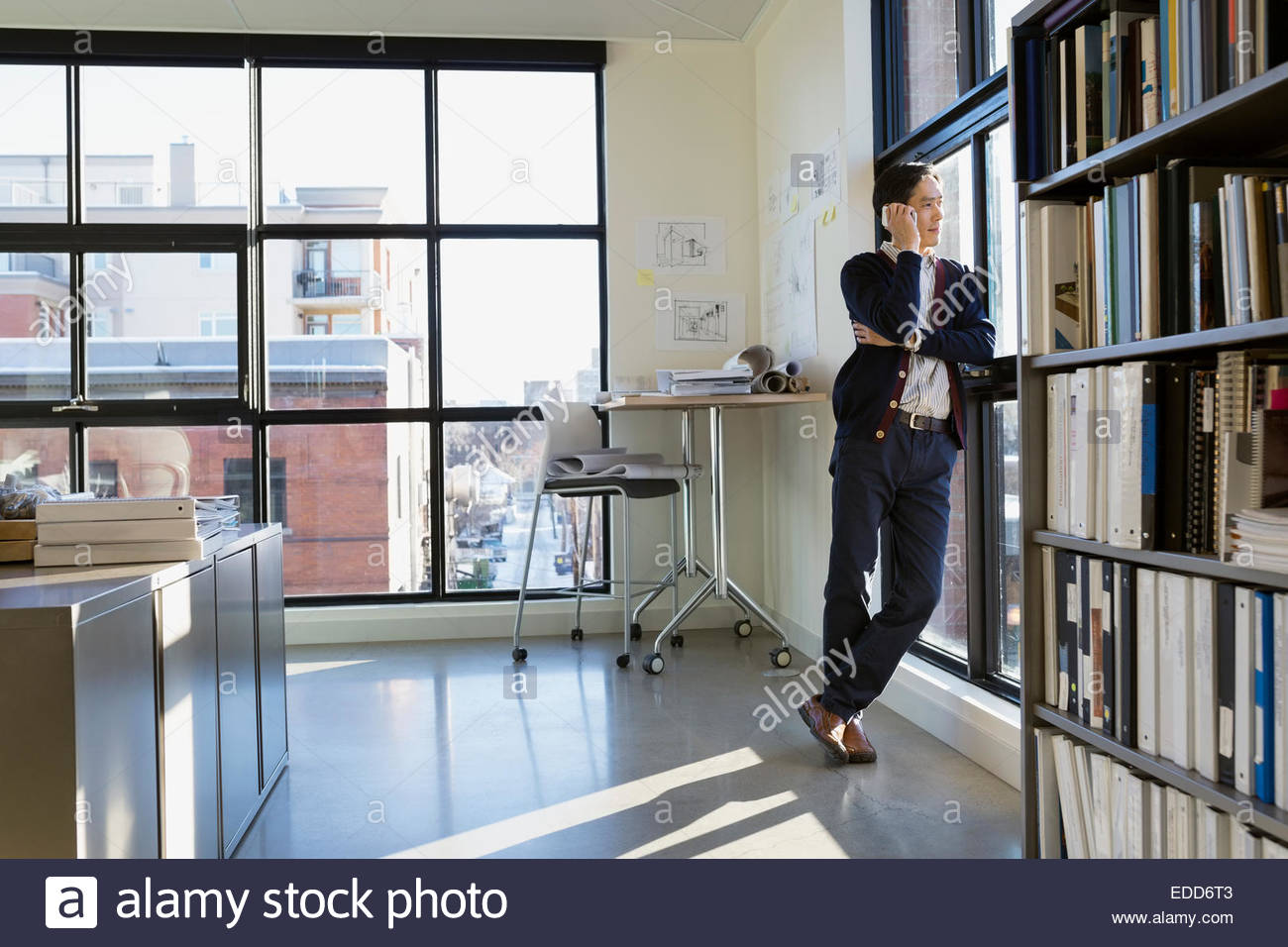Businessman talking on cell phone at office window - Stock Image