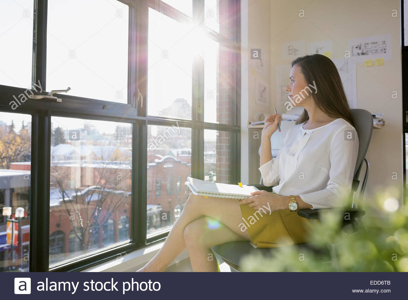 Pensive businesswoman looking out sunny office window - Stock Image