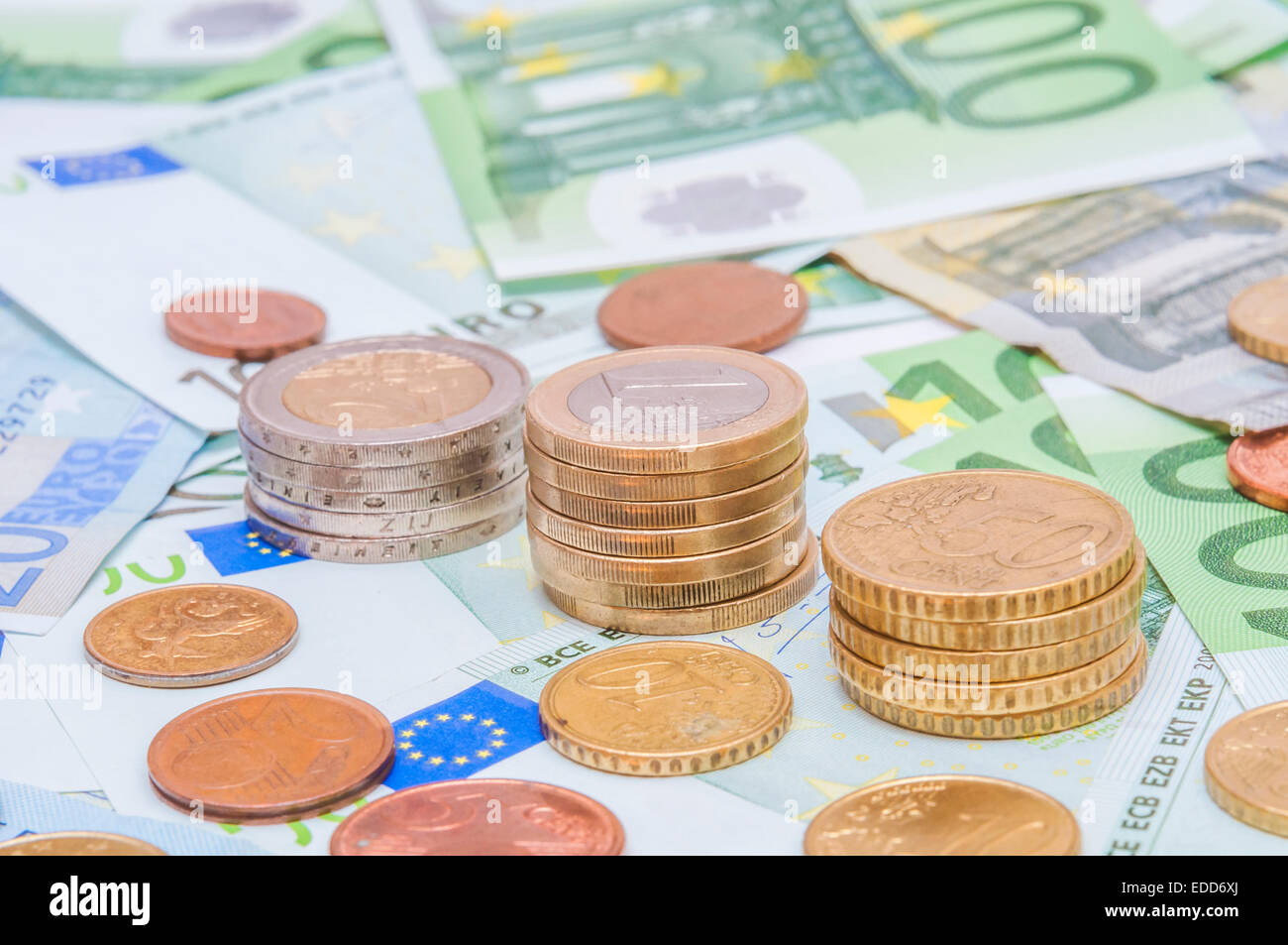Euro banknotes and euro coins in simple example of unpredictable prognoses. - Stock Image