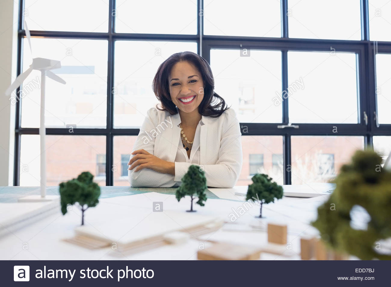 Portrait of confident architect with models and blueprints - Stock Image