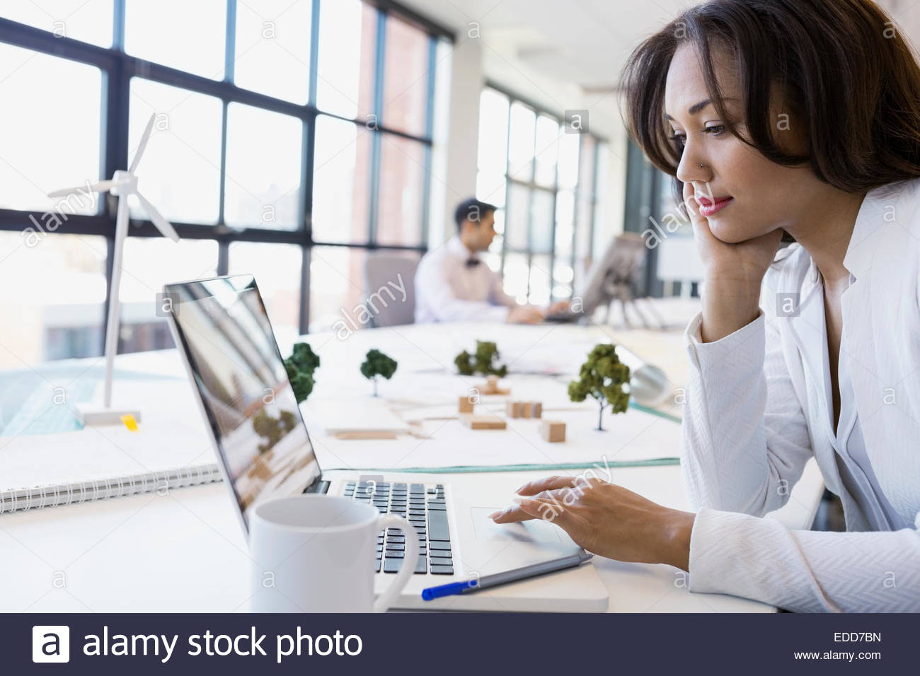 Focused architect working at laptop in office - Stock Image