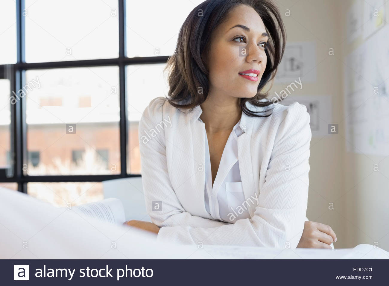 Pensive architect looking away in office - Stock Image