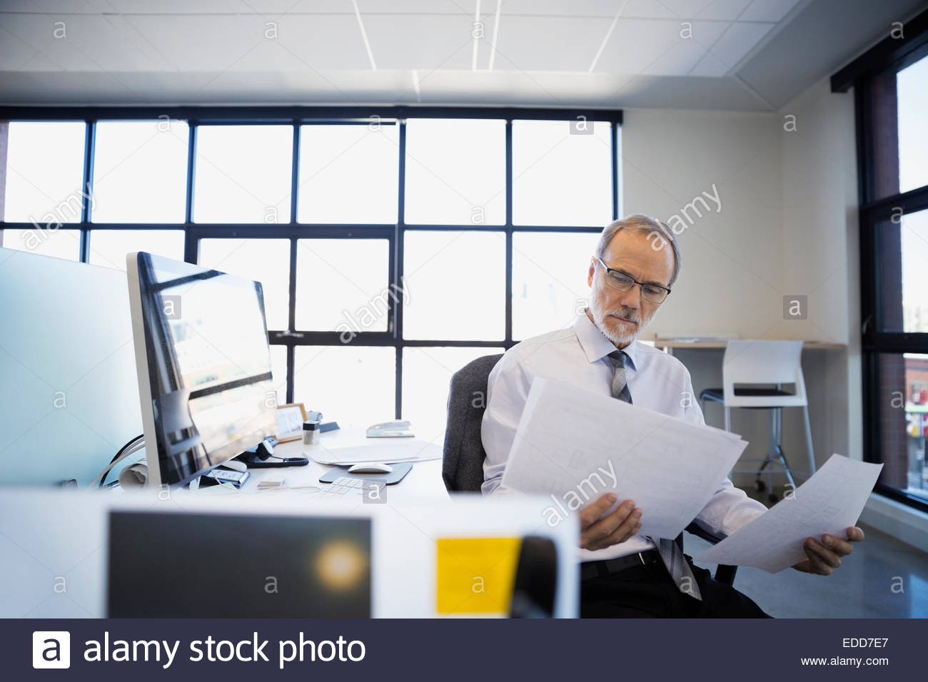 Architect reviewing plans in office - Stock Image