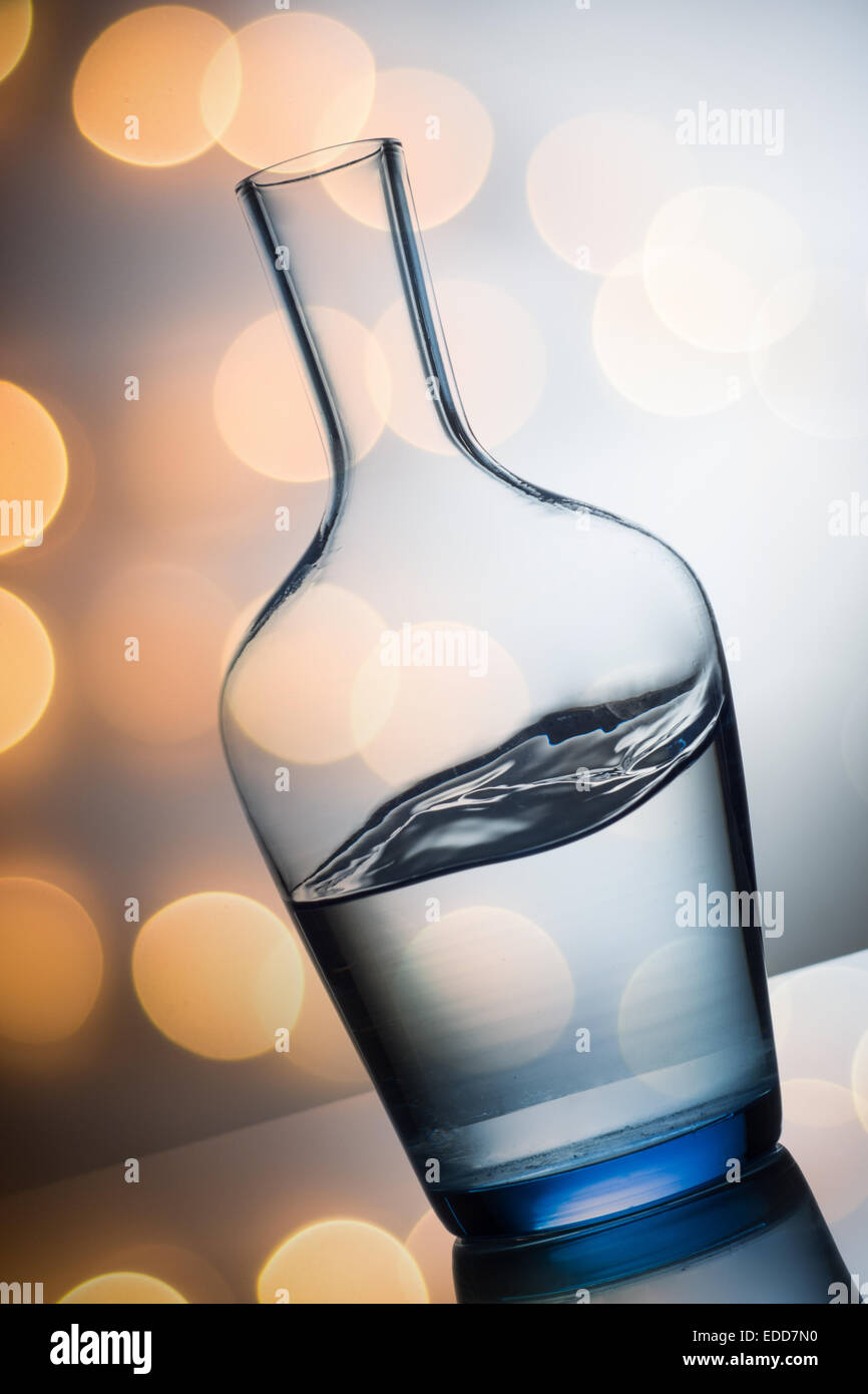 water splash in glass on colorfull light background - Stock Image