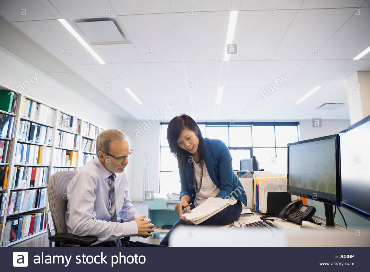 Business people discussing paperwork at desk in office - Stock Image