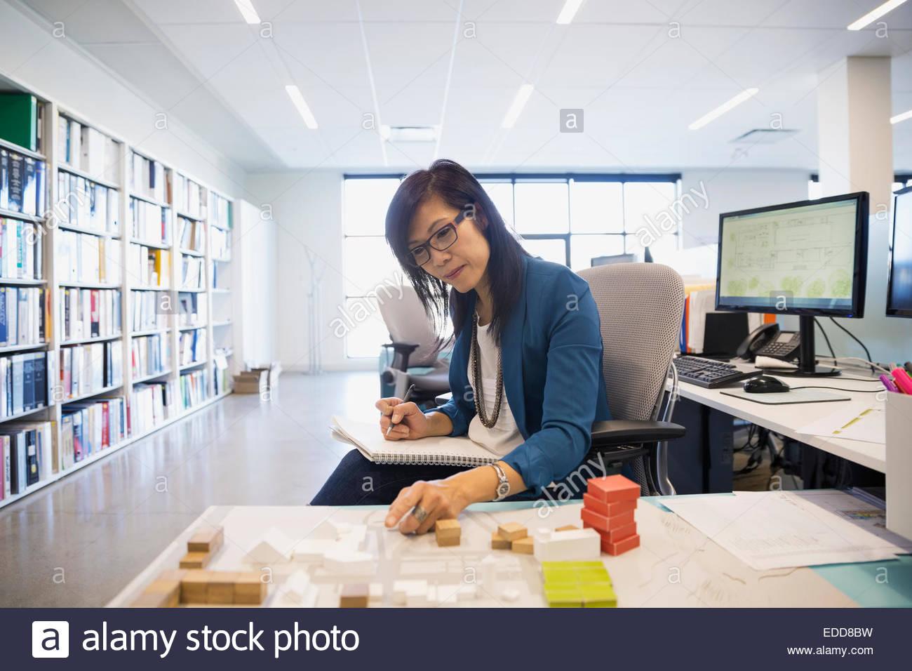 Architect examining model in office - Stock Image