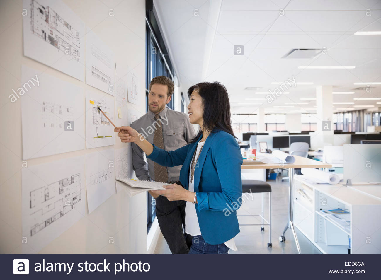 Architects discussing plans at wall - Stock Image
