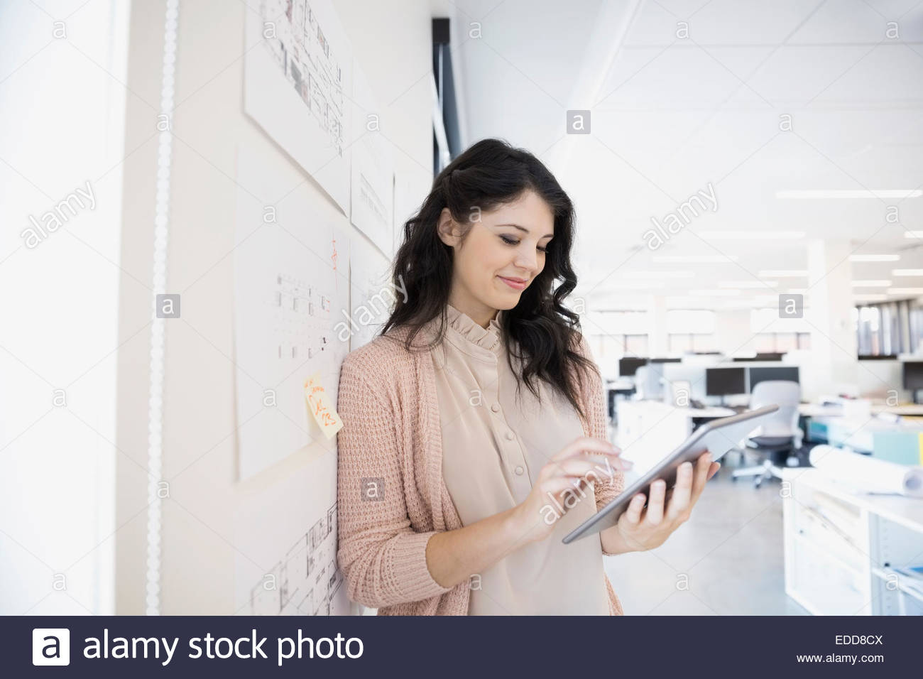 Smiling architect using digital tablet at wall - Stock Image
