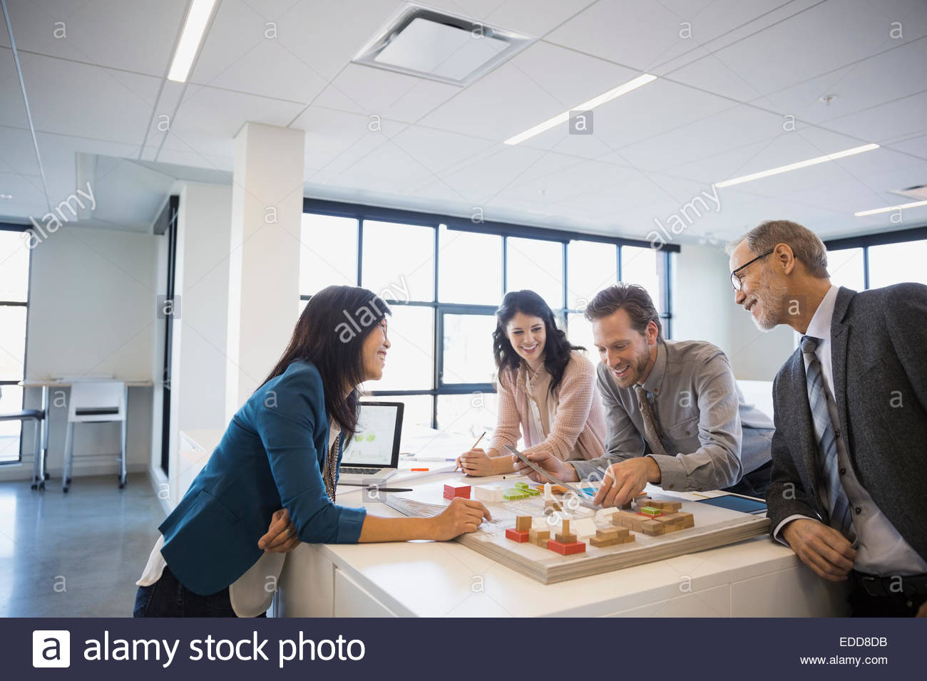 Architects meeting around model in office - Stock Image