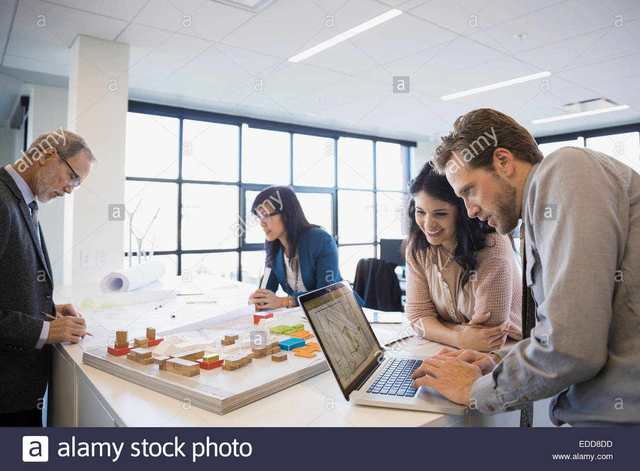Architects working on laptop near model in office - Stock Image
