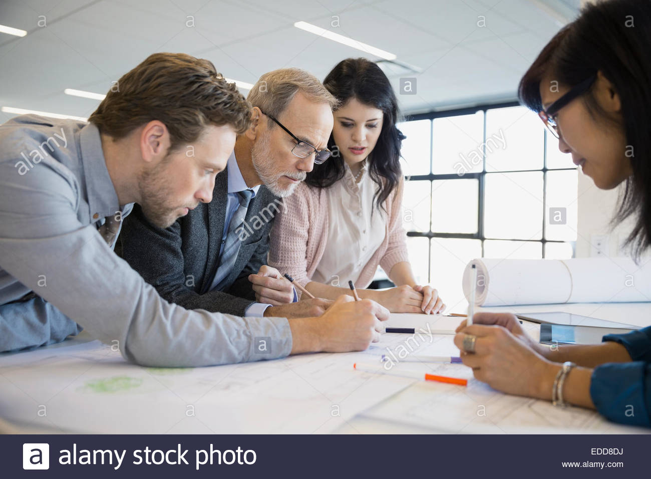 Architects drafting blueprints in office - Stock Image