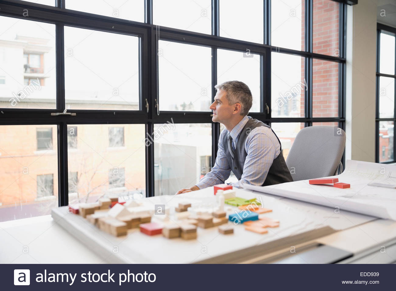 Pensive architect looking out office window - Stock Image