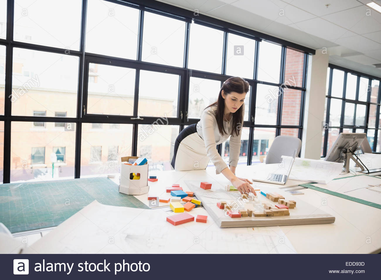 Architect working at model in office - Stock Image