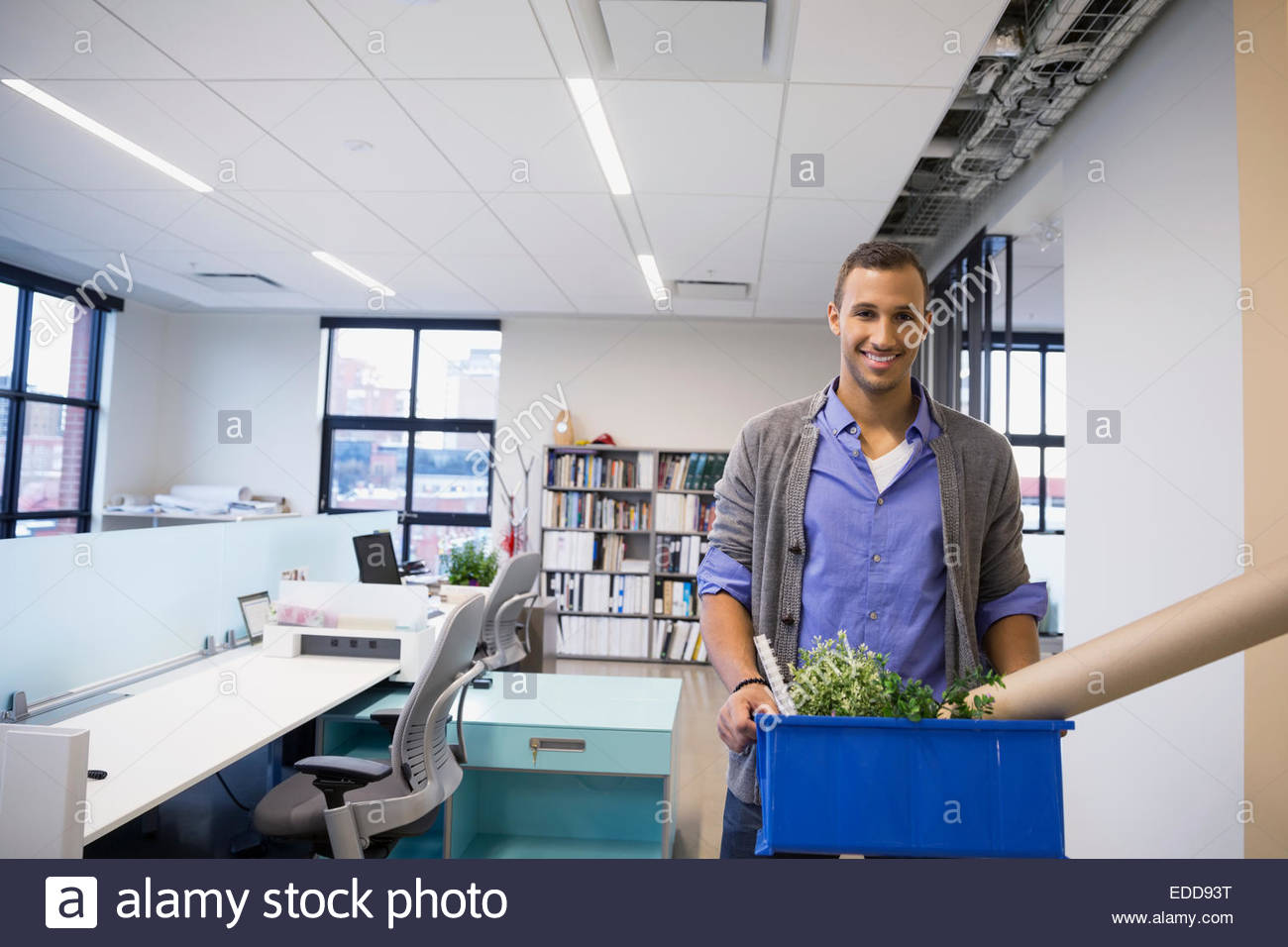 Portrait of smiling businessman carrying belongings in office - Stock Image