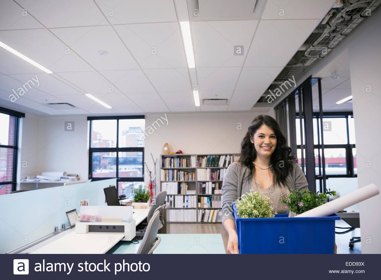 Portrait of smiling businesswoman carrying belongings in office - Stock Image