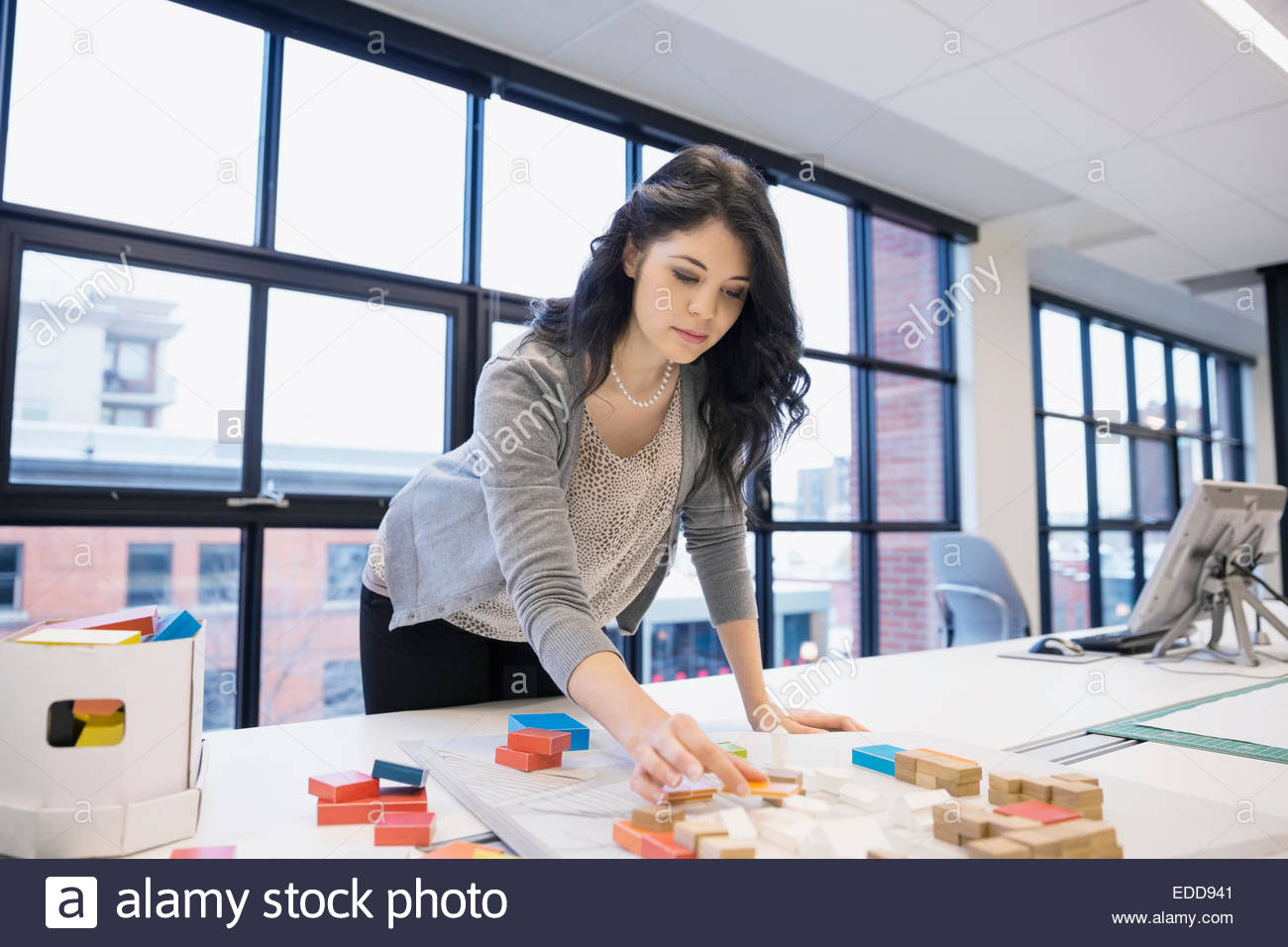 Architect arranging model in office - Stock Image