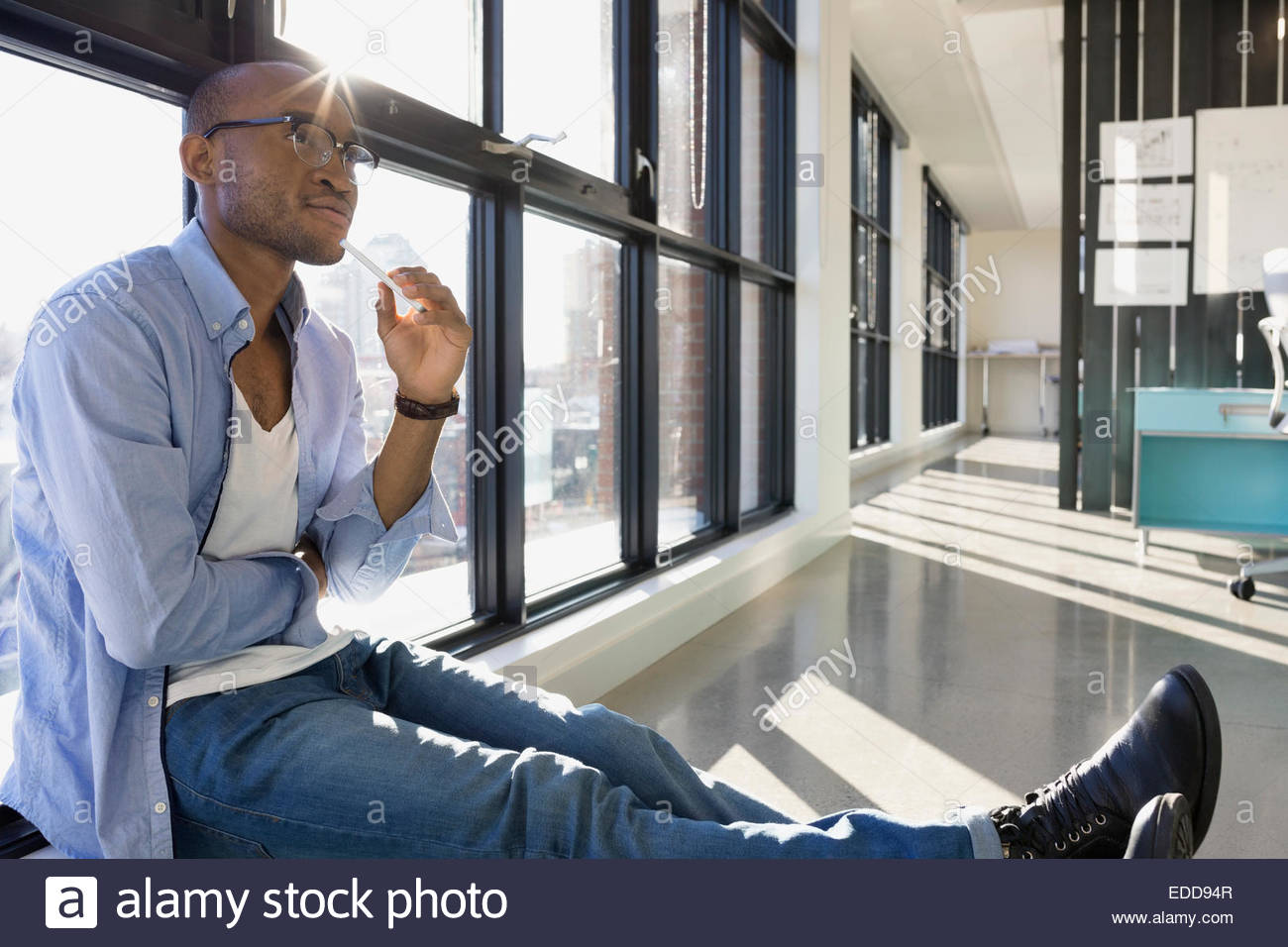 Pensive businessman at window in office - Stock Image