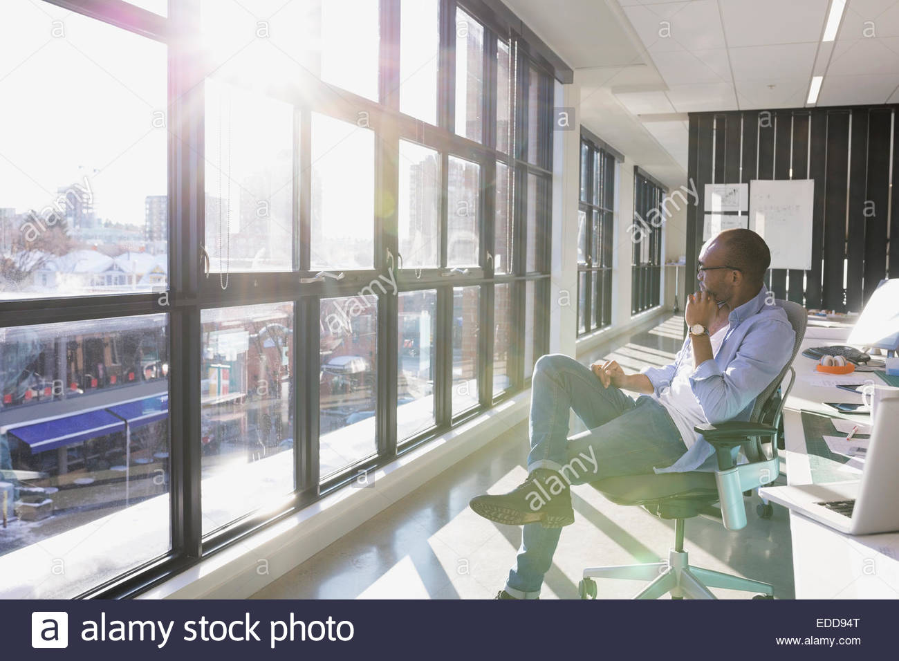 Pensive businessman looking out sunny office window - Stock Image