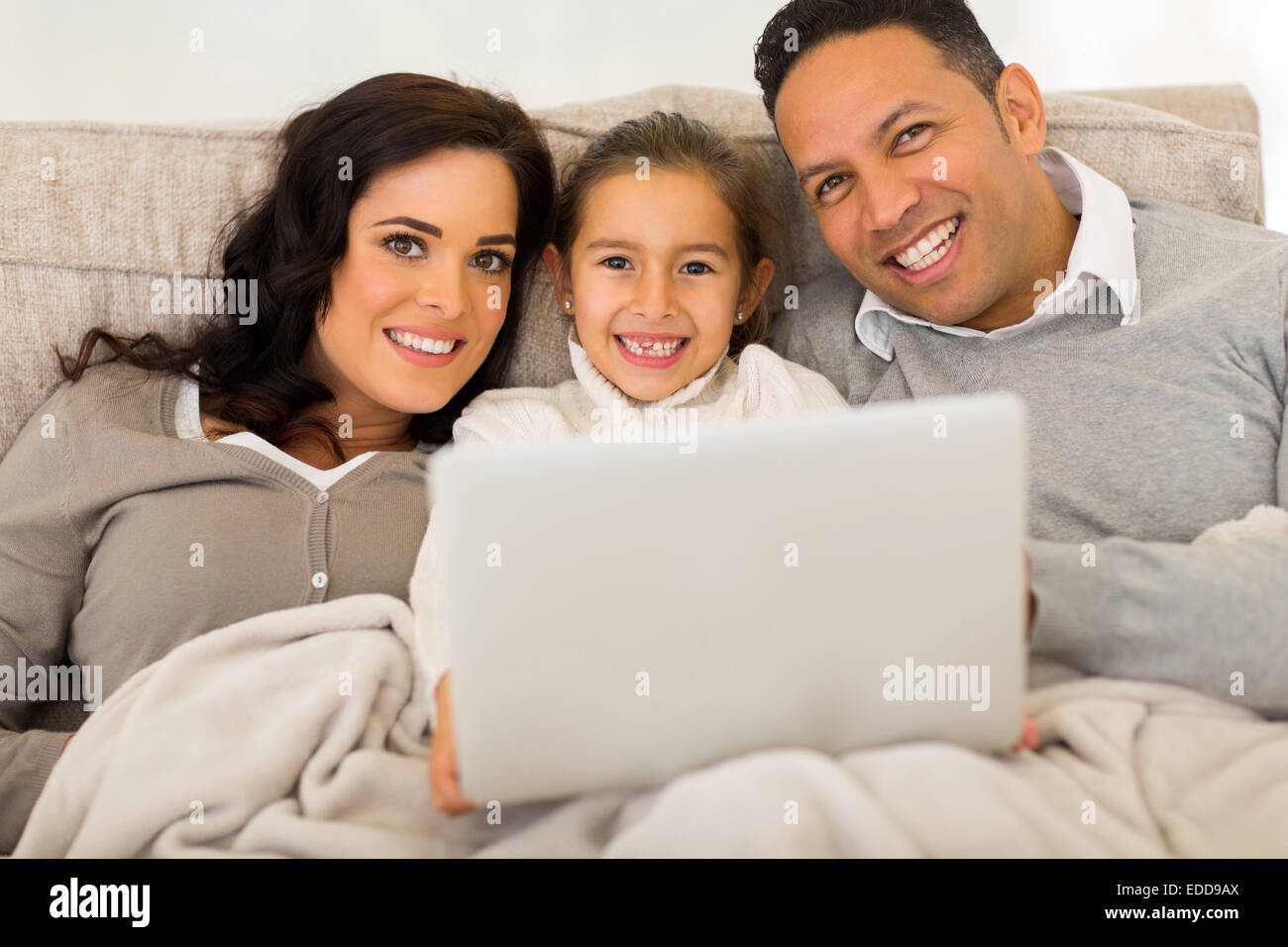 Cute family of three using laptop computer while relaxing on sofa at home