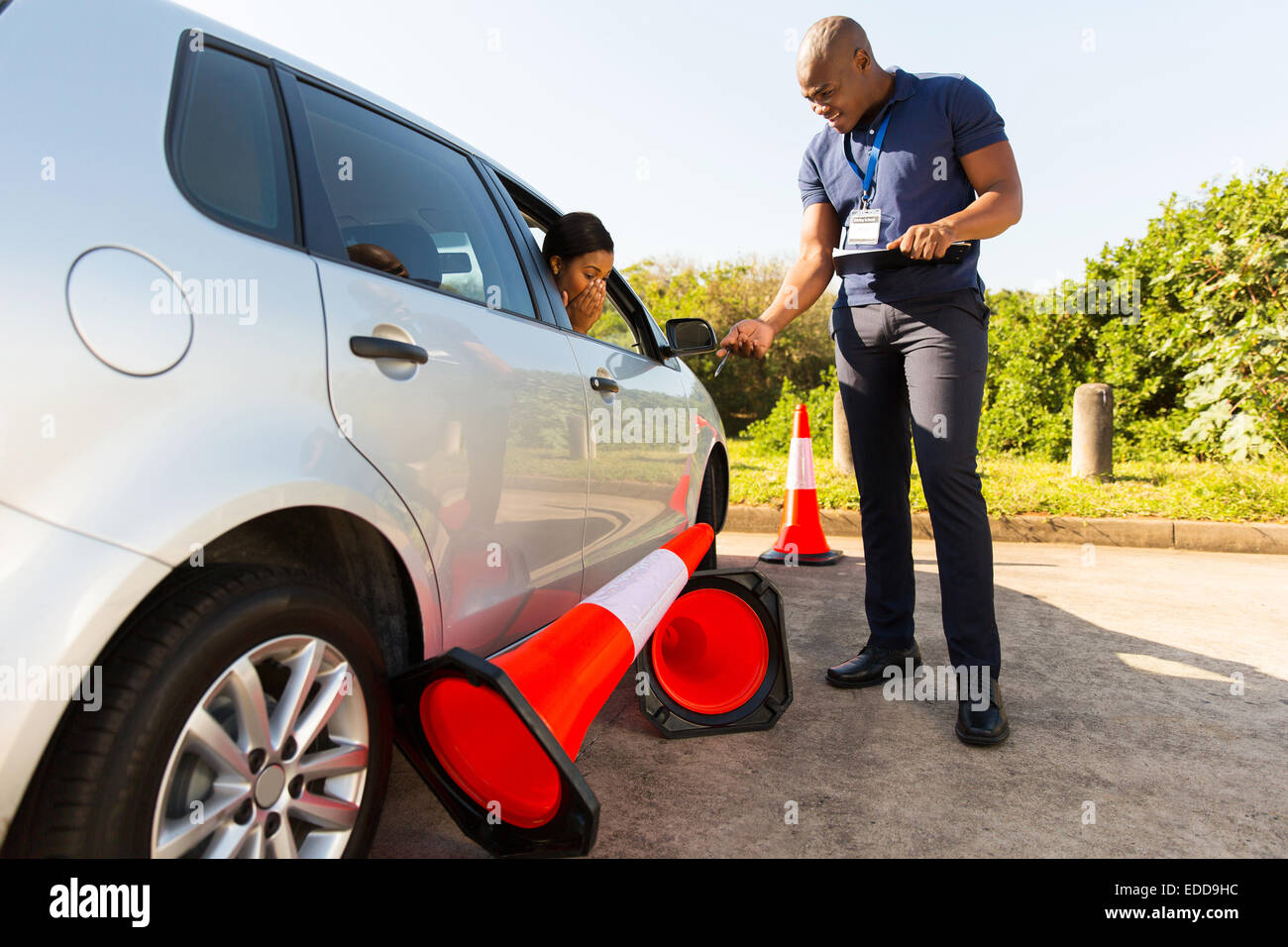 student driver making mistake during driving test, running over traffic cones - Stock Image