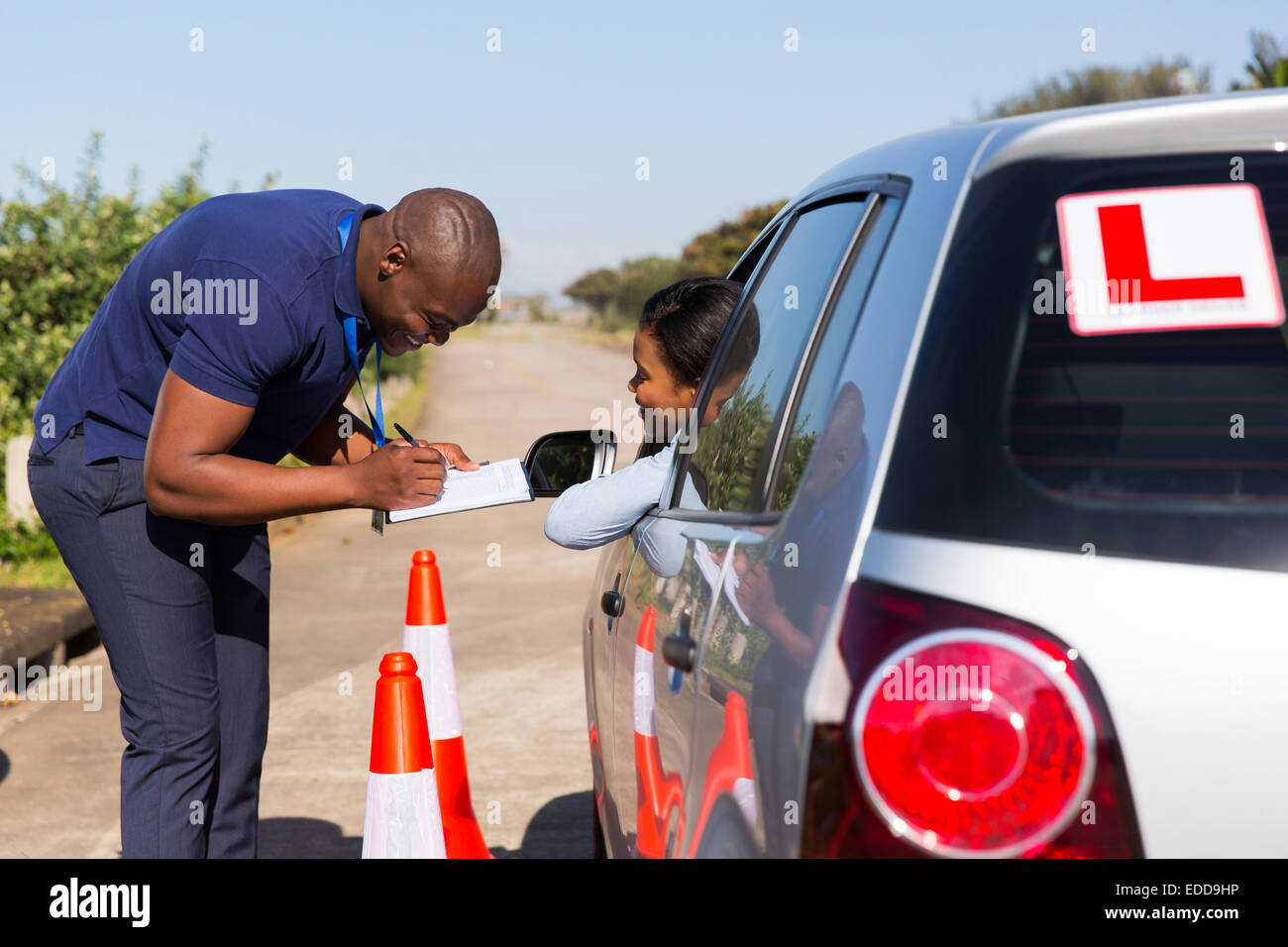 male African driving instructor and student driver in testing ground - Stock Image