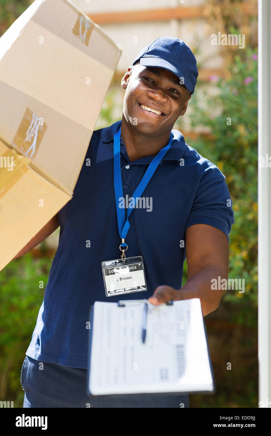 African delivery man carrying parcel and presenting receiving form - Stock Image